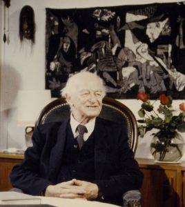 Linus Pauling vor einem Wandbild von Pablo Picasso Guernica.